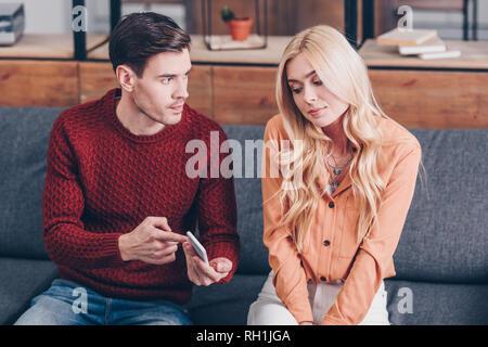 Jeune homme jaloux montrant smartphone pour confondre young woman sitting on couch Banque D'Images