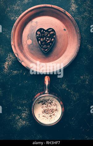 Coeur de grains de café et de café verre dans une tasse vintage on a rustic fond sombre. Valentine's Day.vue d'en haut. Banque D'Images