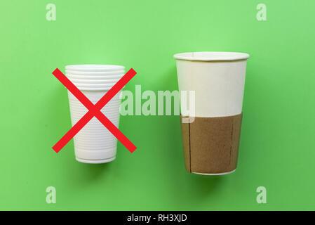 En plastique à usage unique blanc et tasse de papier sur un fond vert. La notion de choix sans plastique ou les problèmes environnementaux. Banque D'Images