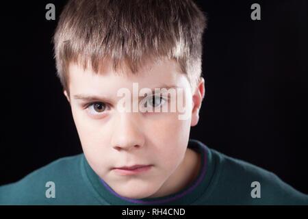 Studio coups de jeune garçon avec des cheveux bruns courts, portant des cavalier vert Banque D'Images
