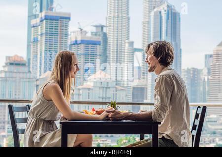 Couple aimant prendre le petit déjeuner sur le balcon. Table de petit-déjeuner avec café et fruits pain croisant sur un balcon dans le contexte de la grande ville