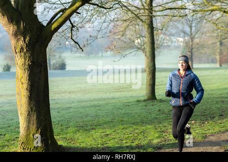 Femme sur l'hiver tôt le matin à travers Park rester en forme grâce à l'exercice