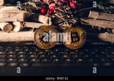 Bitcoin lumineux debout sur le clavier avec fond de noël. Or deux chrstimas bitcoins au moment sur fond de bois.