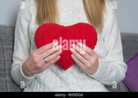 Young Girl holding big red coeur dans la main sur sa poitrine à la maison. Girl in white sweater. Femme jour et Valentines Day concept. Close up Banque D'Images