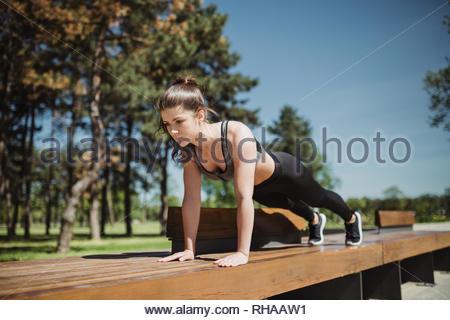 Belle brunette woman femme caucasienne sportive s'étirer après l'exécution de l'extérieur. La motivation de remise en forme. Sportif en bonne santé girl stretching en parc sur sunny Banque D'Images