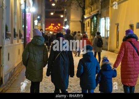 Les touristes à pied à travers la ville de nuit en hiver. Une femme et quatre enfants. Banque D'Images