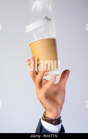 Main d'un homme d'affaires dans une veste bleue, chemise blanche et regarder les captures une tasse de café chaud avec de la vapeur d'un verre. Pause café co publicité Banque D'Images
