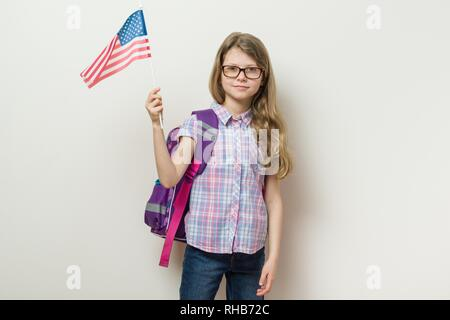 Enfant de l'école avec un sac à dos tient le drapeau USA, arrière-plan lumineux mur dans l'école. Banque D'Images