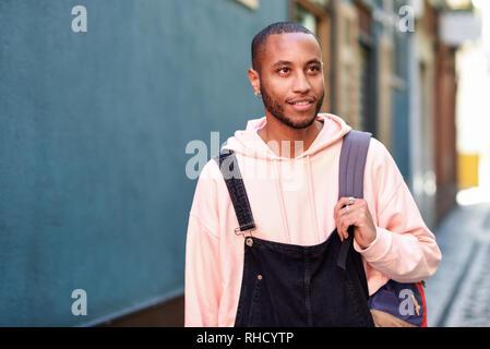 Jeune homme noir souriant à pied dans la rue.
