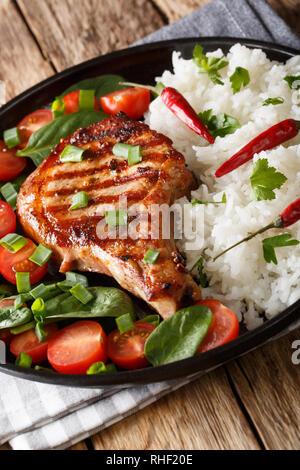Steak de porc grillé avec du riz et garnir de salade de légumes frais sur une plaque verticale. Banque D'Images