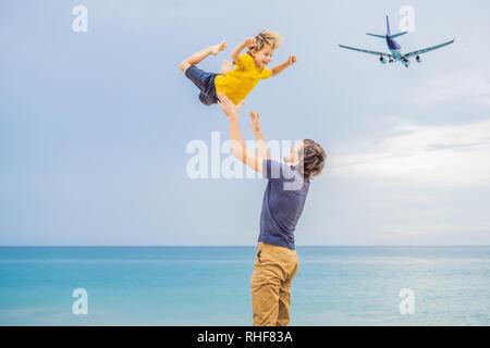 Père et fils s'amuser sur la plage en regardant l'atterrissage des avions. Voyager en avion avec des enfants concept Banque D'Images