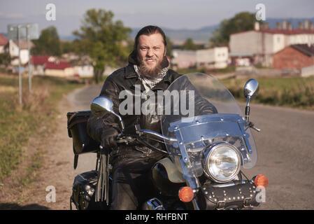 Portrait of handsome happy smiling biker barbu en veste de cuir noir assis sur moto moderne sur les pays sur fond flou de petite ville bâtiments sur journée ensoleillée. Banque D'Images