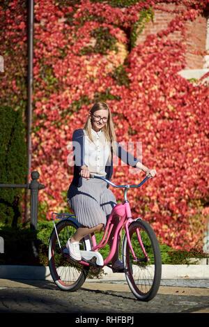 Young happy smiling blonde cheveux long femme en vêtements décontractés et lunettes vélo dame rose location sur bright chaude journée ensoleillée sur fond de mur couvert de belles feuilles de lierre rouge. Banque D'Images