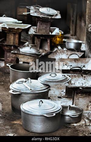 Groupe de réchauds à charbon de bois rustique et une batterie de cuisine, casseroles et poêles sur le plancher sur le marché local de Toliara, Madagascar. Banque D'Images