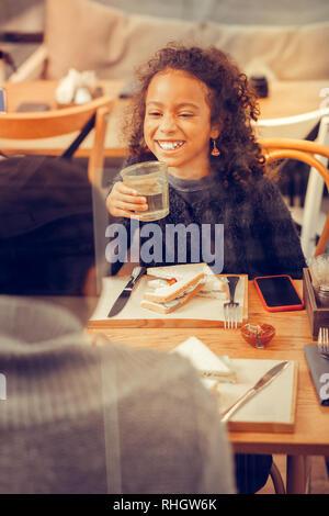 Girl laughing tandis que l'eau potable dans les restaurant et parlant avec les parents Banque D'Images
