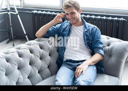 Jeune homme heureux assis détendu sur canapé et parler au téléphone. Banque D'Images