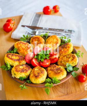 La pomme de terre et de fromage fait maison ruddy escalopes, décoré avec des tomates et le persil frais, dans une plaque en céramique sur une carte en bois Banque D'Images