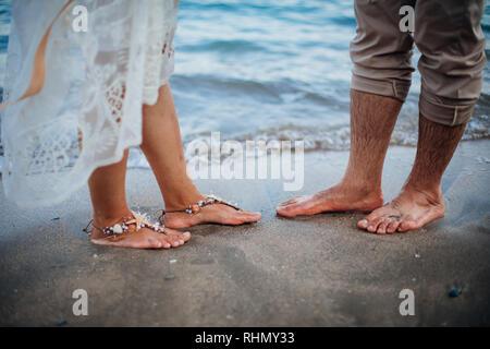 Mariée et le marié en train de marcher sur la plage. L'homme et de la femme, les pieds dans le sable. Mariage à la plage Banque D'Images