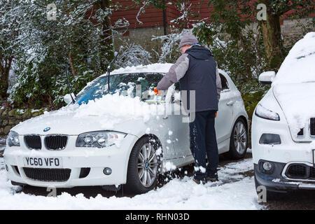 L'homme dépose la neige des pare-brise de voiture BMW après une nuit de neige lourde à Glencoe, Highlands, Scotland en Janvier Banque D'Images