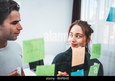 Équipe de gestionnaires de projets ayant réunion au bureau moderne. Des collègues de la discussion de nouvelles idées et à l'aide de verre mur note collante