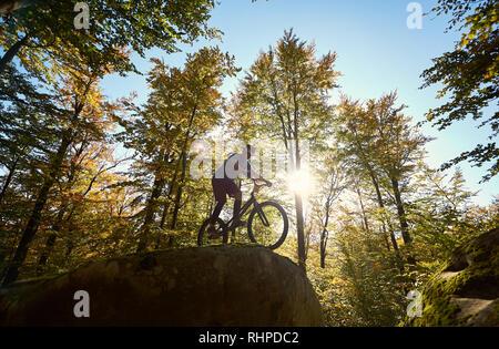 Mâle actif cyclist riding on trial location, ce truc acrobatiques sur big boulder dans la forêt sur une journée ensoleillée d'été. Concept d'extreme sport dangereux Banque D'Images