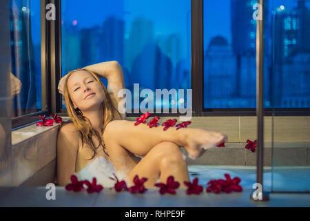 Jeune femme assise dans un bain de mousse et de fleurs de frangipanier dans le contexte d'une fenêtre panoramique donnant sur les gratte-ciel et un grand soir Banque D'Images