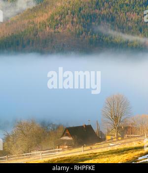 Matin ensoleillé paysage avec cabane en bois dans les montagnes couvertes de brume, Carpates, Ukraine Banque D'Images