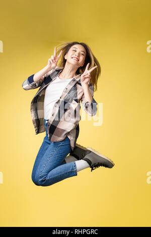 Toute la longueur verticale de la taille du corps studio photo portrait de jolie réussite insouciante heureux étudiant dame lui montrer que v-sign près de yeux visage sauter de haut. Banque D'Images