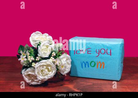 Magnifique bouquet de fleurs arrangées et un présent avec un message 't'aime Maman' sur une table en bois. La fête des mères, Pâques, Saint-Valentin, anniversaire, Christ Banque D'Images