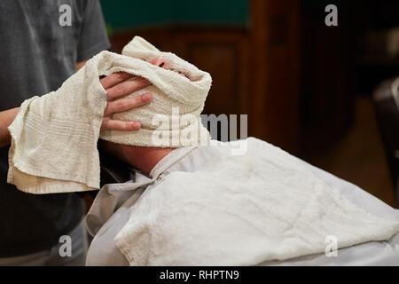 Rituel traditionnel de raser la barbe avec des compresses chaudes et froides dans un ancien style de coiffure Banque D'Images