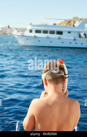 Un garçon est mise sur un masque de plongée prêt à nager dans la mer. Yacht blanc est sur l'arrière-plan Banque D'Images
