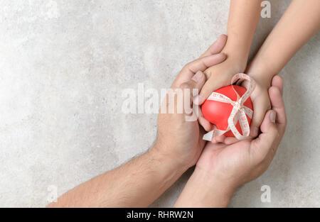Le père et l'enfant hands holding cœur rouge sur fond de marbre, soins de santé, l'amour, donner de l'espoir et concept de famille, Banque D'Images
