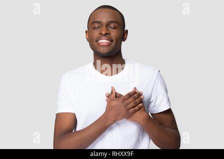 Reconnaissant happy african man holding hands sur la poitrine sentiment satisfaction