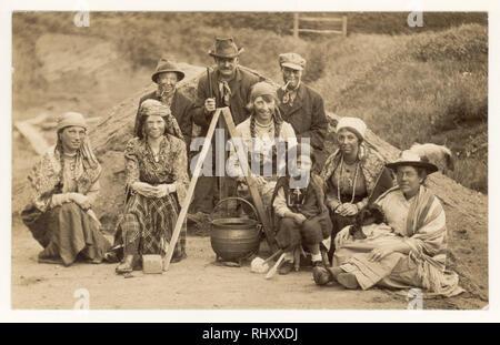 Début des années 1900 Carte postale de famille habillés comme des gitans en vêtements traditionnels, visages noircis, stitting à côté de casserole, posant pour une photo de groupe, au Royaume-Uni vers 1920 Banque D'Images