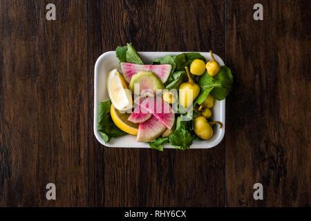 Paquet de salade avec Pickle turc, radis, persil et citron dans un coffret plastique contenant. L'alimentation biologique. Banque D'Images