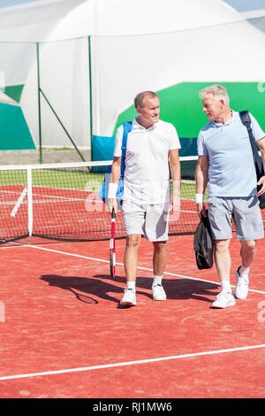 Longueur totale d'hommes en vêtements de sport à parler tout en marchant sur un court de tennis en été, week-end Banque D'Images