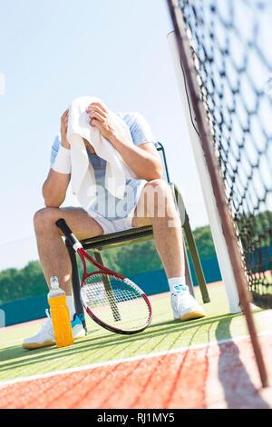 Toute la longueur de l'épuisé man with head in towel assis sur une chaise en filet au tennis sur sunny day Banque D'Images