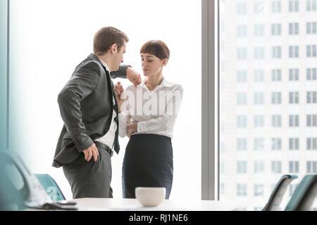 Business couple parler debout contre la fenêtre dans salle de conférence Bureau moderne Banque D'Images