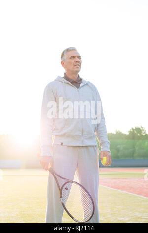 Retour allumé de certain couple avec raquette de tennis et la balle sur le court contre ciel clair Banque D'Images