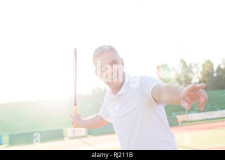 Retour allumé de man swinging raquette de tennis sur le court contre ciel clair Banque D'Images