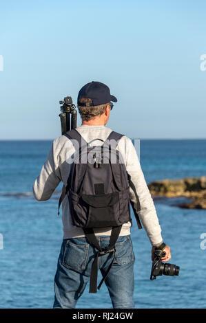 Vue arrière d'un trépied un photographe et l'appareil photo, face à la mer. Banque D'Images