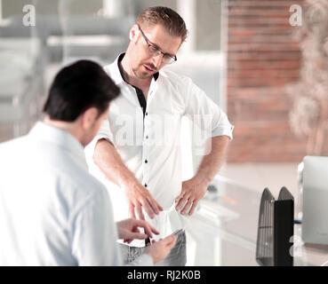 Deux employés discuter de l'information à partir d'un téléphone mobile Banque D'Images