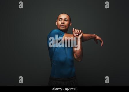 Portrait de jeune homme fort musclé s'étendant ses bras. African Male fitness model debout sur fond sombre