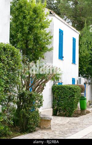 Journée ensoleillée sur la rue de l'ancienne ville grecque, maisons blanches, volets bleu et un toit de tuiles Banque D'Images
