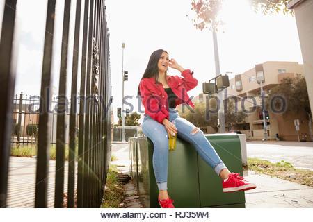 Latinx insouciante jeune femme assise sur l'électricité fort Banque D'Images
