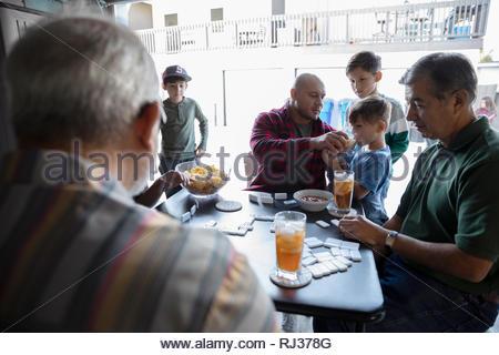 Latinx multi-generation family playing dominos en garage Banque D'Images
