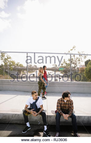 Les jeunes femmes Latinx vérifiant les hommes assis sur le trottoir de passage Banque D'Images