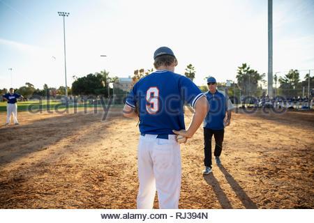 Parler à l'entraîneur de baseball sur terrain ensoleillé Banque D'Images