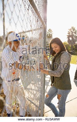 Joueur de baseball Latinx parler avec smiling girlfriend à clôture ensoleillée Banque D'Images