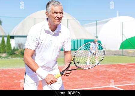 Certain couple avec raquette de tennis contre ami jouer match de double sur cour Banque D'Images